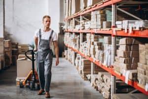 עובד מחסן מסתכל על מדפים תעשייתים